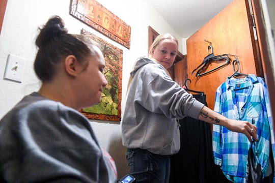 Caregiver Sara Overby helps Kendra Creek sort through clothing to take to Kendra's new apartment in December of last year. Kendra was leaving her family home for the first time to live with boyfriend Wade Conway.