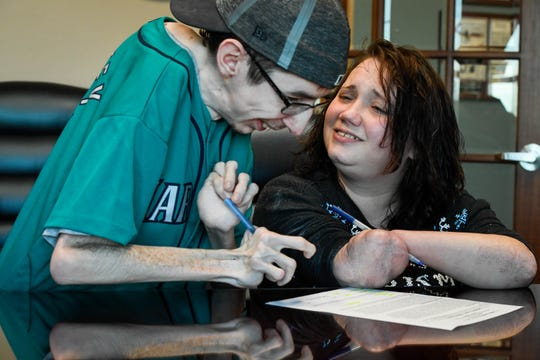 Wade Conway and Kendra Creek sign the papers for their new apartment last December. It was the first big step towards independence.