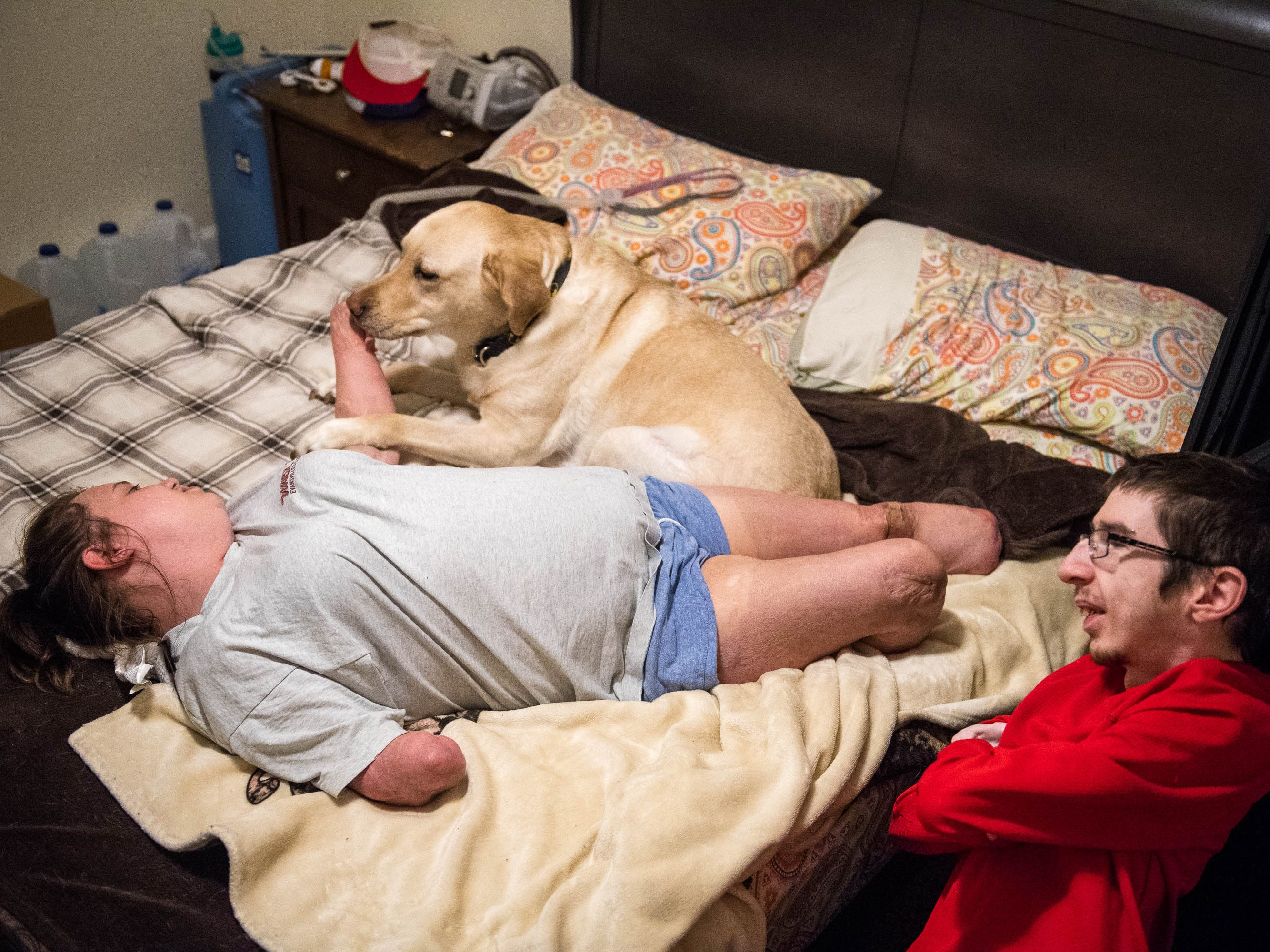 Kendra Creek and Wade Conway spend time with Wade's service dog, Dagwood. Wade, born with arthrogryposis multiplex congenita, and Kendra, whose bacterial meningitis left her a quadruple amputee, spend their evenings without a caregiver in the apartment the couple  shares.