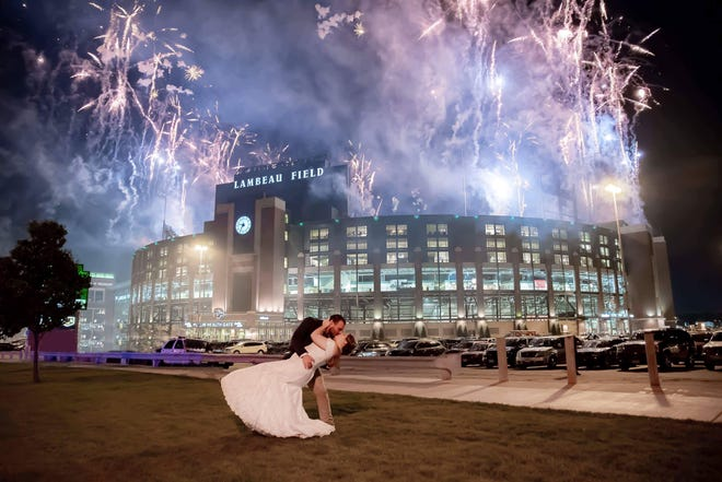 Mike and Kassandra Anderson of Little Suamico capped off their wedding day on Saturday with a photo outside Lambeau Field during the Family Night fireworks.