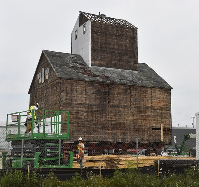 Workers help to secure the historic granary on Monday, Aug. 6, 2018, to prevent birds from entering the structure located on the corner of Oregon and 1st streets in Sturgeon Bay. There is an owl decoy on top to ward off birds and other creatures. Tina M. Gohr/USA TODAY NETWORK-Wisconsin