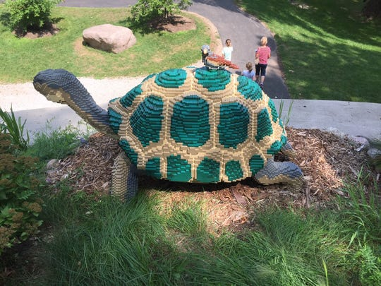 "A Galapagos tortoise with a Darwin finch made from 23,317 Legos sits on top of the Hobbit House as part of the ""Nature Connects: Art with Lego Bricks""  exhibit at Green Bay Botanical Garden."