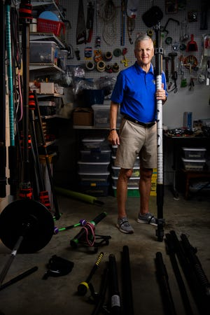 Gordon Brown, inventor of the Tsunami Bar, poses for a portrait with one of his flexible barbells in his workshop on Friday, Aug. 3, 2018.