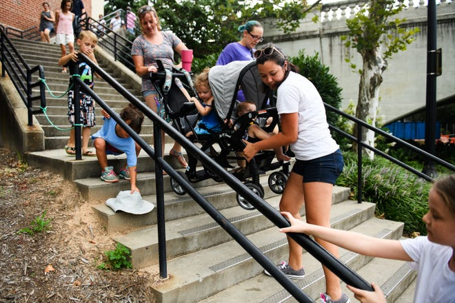 Melanie Roach helps Elysa Goldstein carry Makailah Goldstein, 3, and her brother Noah, 1, in their stroller during the Breakout Greenville Treasure Hunt in downtown Greenville on Tuesday, Aug. 7, 2018.
