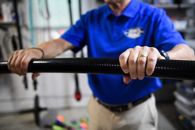 Gordon Brown, inventor of the Tsunami Bar, gives a demonstration of his flexible barbell in his home on Friday, Aug. 3, 2018.