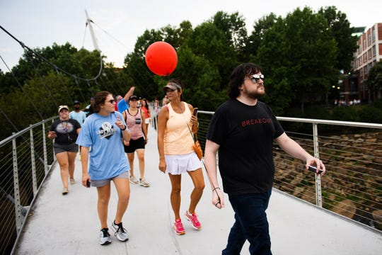 Jon White of Breakout Greenville leads a group across Liberty Bridge during the Breakout Greenville Treasure Hunt on Tuesday, Aug. 7, 2018.