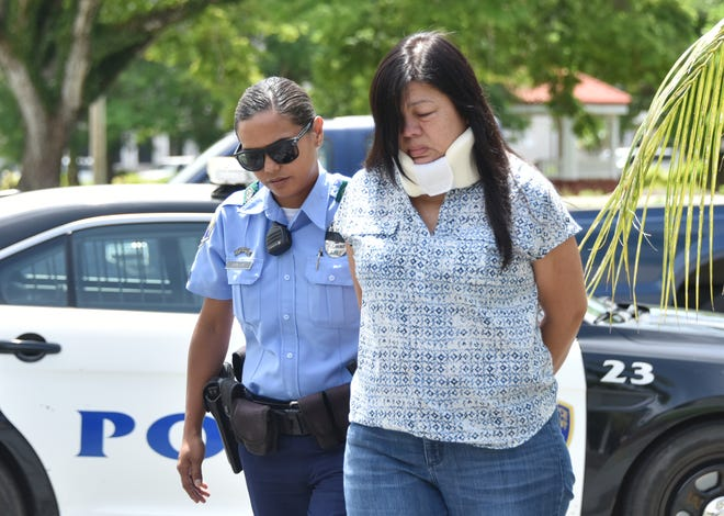 Gracialla Shinohara Shelton is escorted to the Guam Police Department Hagatna precinct by Highway Patrol Division Officer Franki Santos on Aug. 7, 2018.