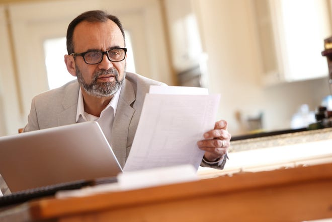 A Hispanic businessman works at home as he sits at his dining room table while he leans forward to look at some paperwork that sits in front of him.  He wears a light colored jacket and a pair of eyeglasses.  The image is captured with a telephoto lens and a selective focus is applied while the camera is tilted slightly off axis.  Light filters in from outside illuminating the kitchen behind him.