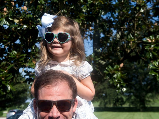 """Tyler Roper with daughter Eleanor at St. John's Episcopal Cathedral's weekly """"Sundays at the Shore"""" service at Lakeshore Park on Sunday, August 5, 2018."""
