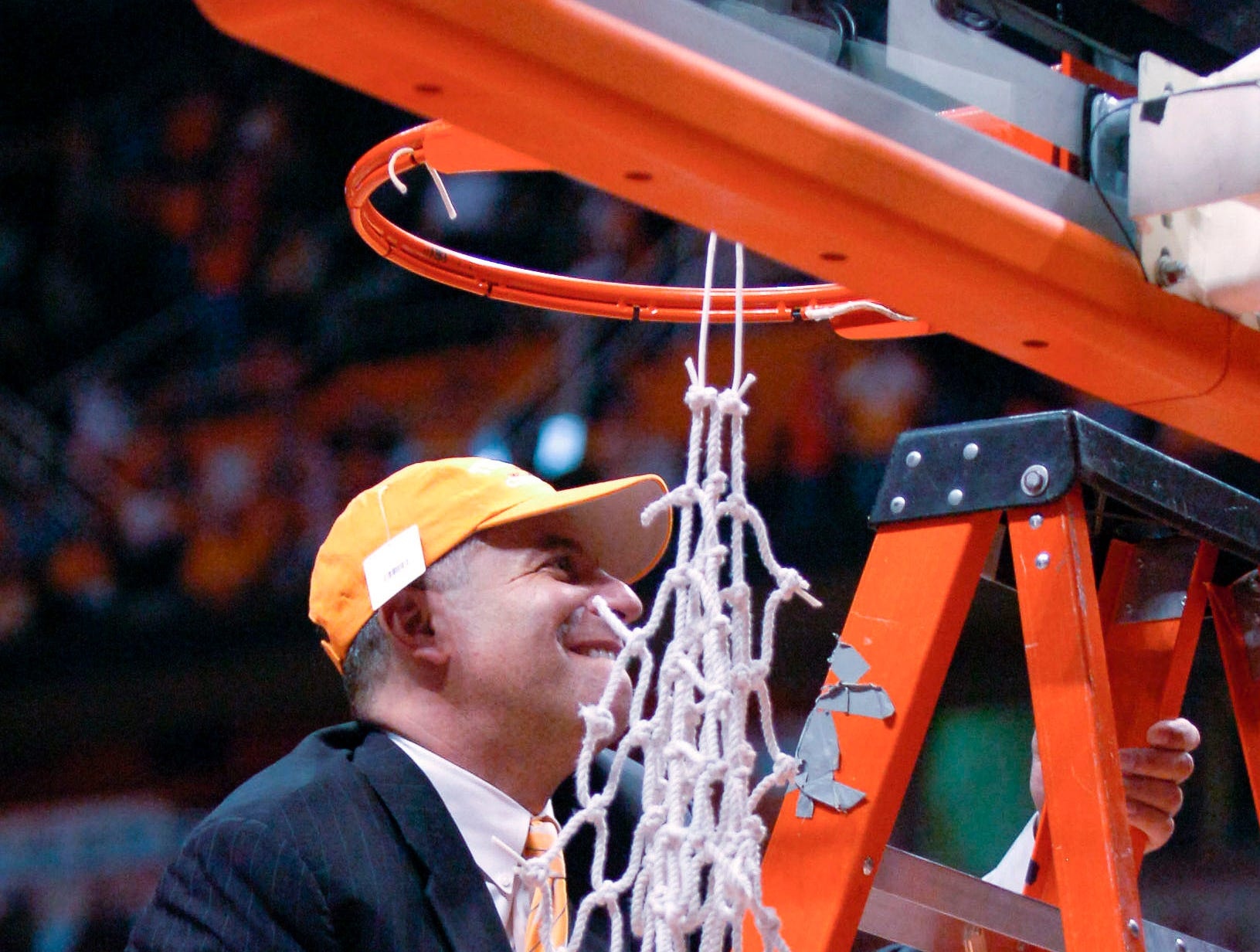 Tennessee head coach Bruce Pearl climbs up to cut a piece of the basketball net down in celebration of the Volunteers first outright SEC title in 41 years in 2008. Tennessee defeated South Carolina 89-56.