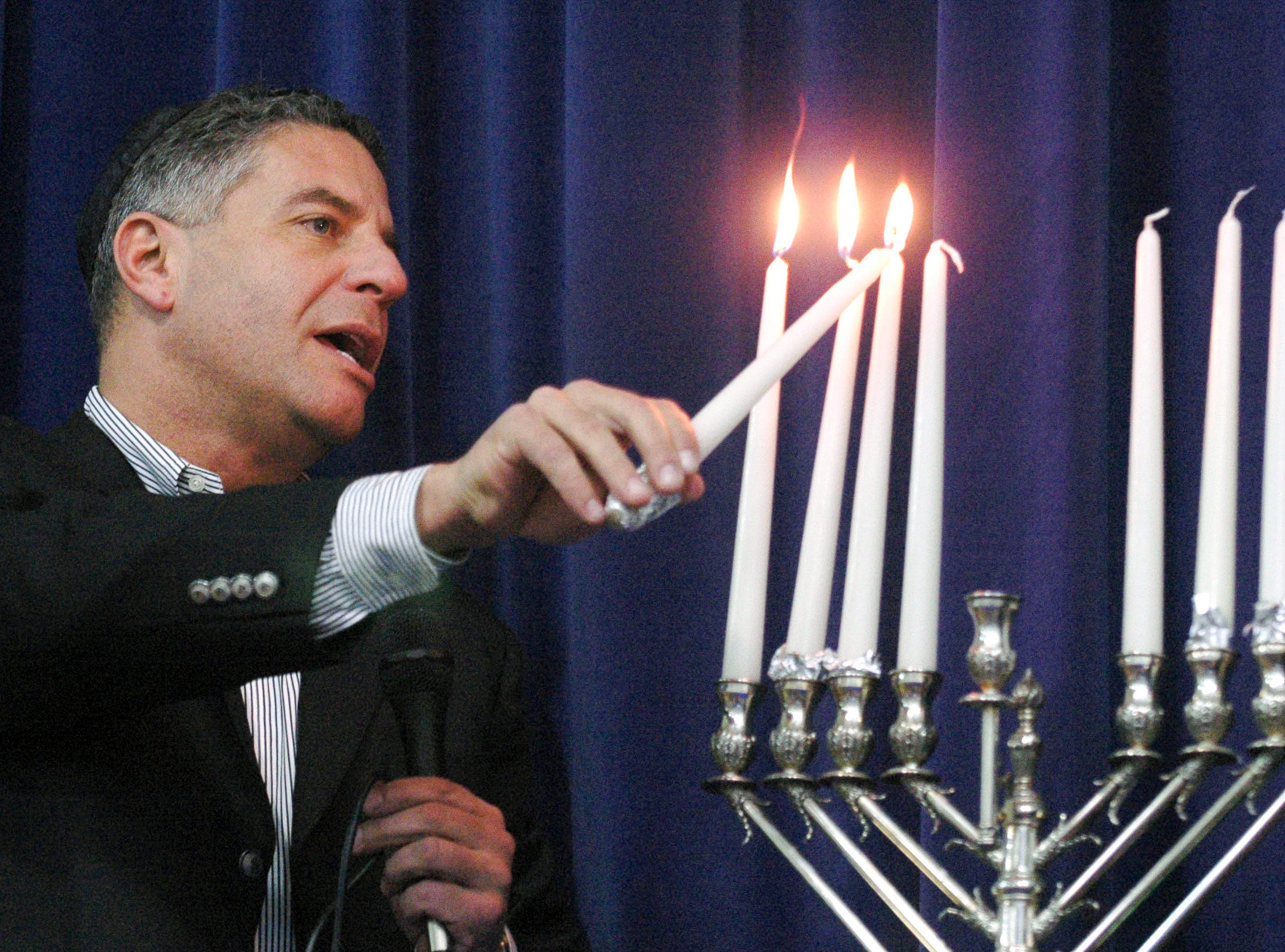 University of Tennessee men's basketball coach Bruce Pearl lights the candles of a Hanukkah Menorah during Menorah Madness at the Arnstein Jewish Community Center in 2007. The event is sponsored by the Knoxville Jewish Alliance and Chabad of Knoxville and marked the final day of Hannukah.