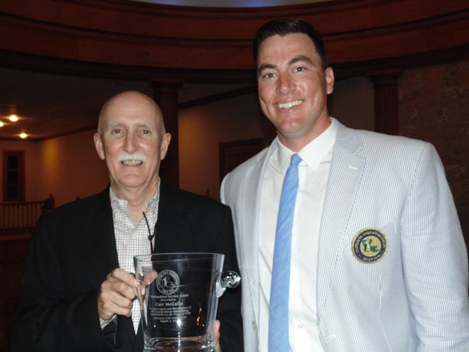 Carr McCalla (left) of Lafayette receives the Louisiana Golf Association's Distinguished Service Award from LGA executive director Logan Ray last Thursday at a banquet prior to the Mid-Amateur Championship. McCalla served for 22 years as the LGA's first full-time executive director.