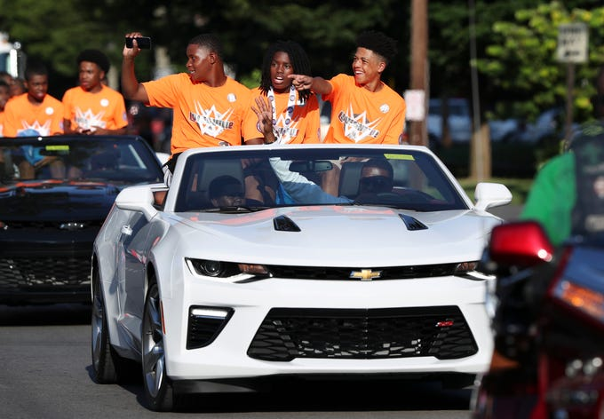 (Right to Left)  Isaiah Green, Stevaun Butler and T.J. Ladd waved at the crowd as they cruised down West Broadway during a parade to celebrate the 13 and Under West Louisville All-Stars advancing to the Babe Ruth World Series in Arkansas.Aug. 6, 2018