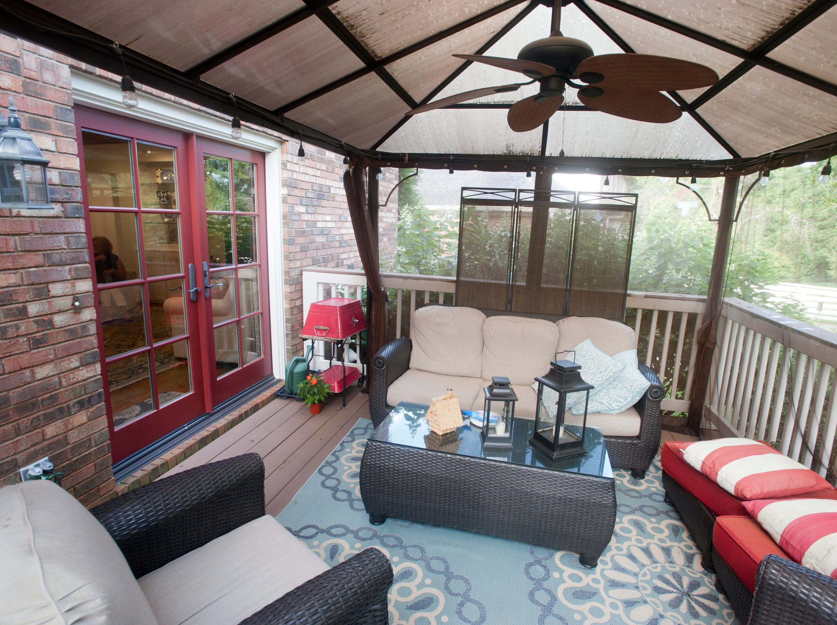 The screened-in back deck at the home of Jean Hodges with French doors to the family room.