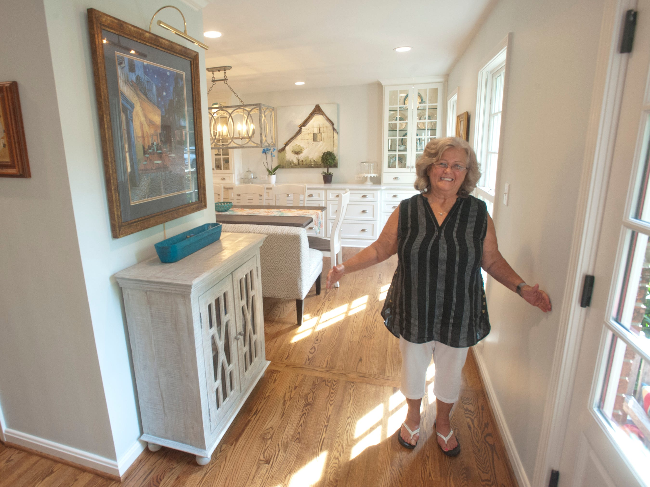 Jean Hodges stands in the opened entrance to her home where a wall and door to the dining room had previously been located.  The new floor plan was created by Bailey Remodeling