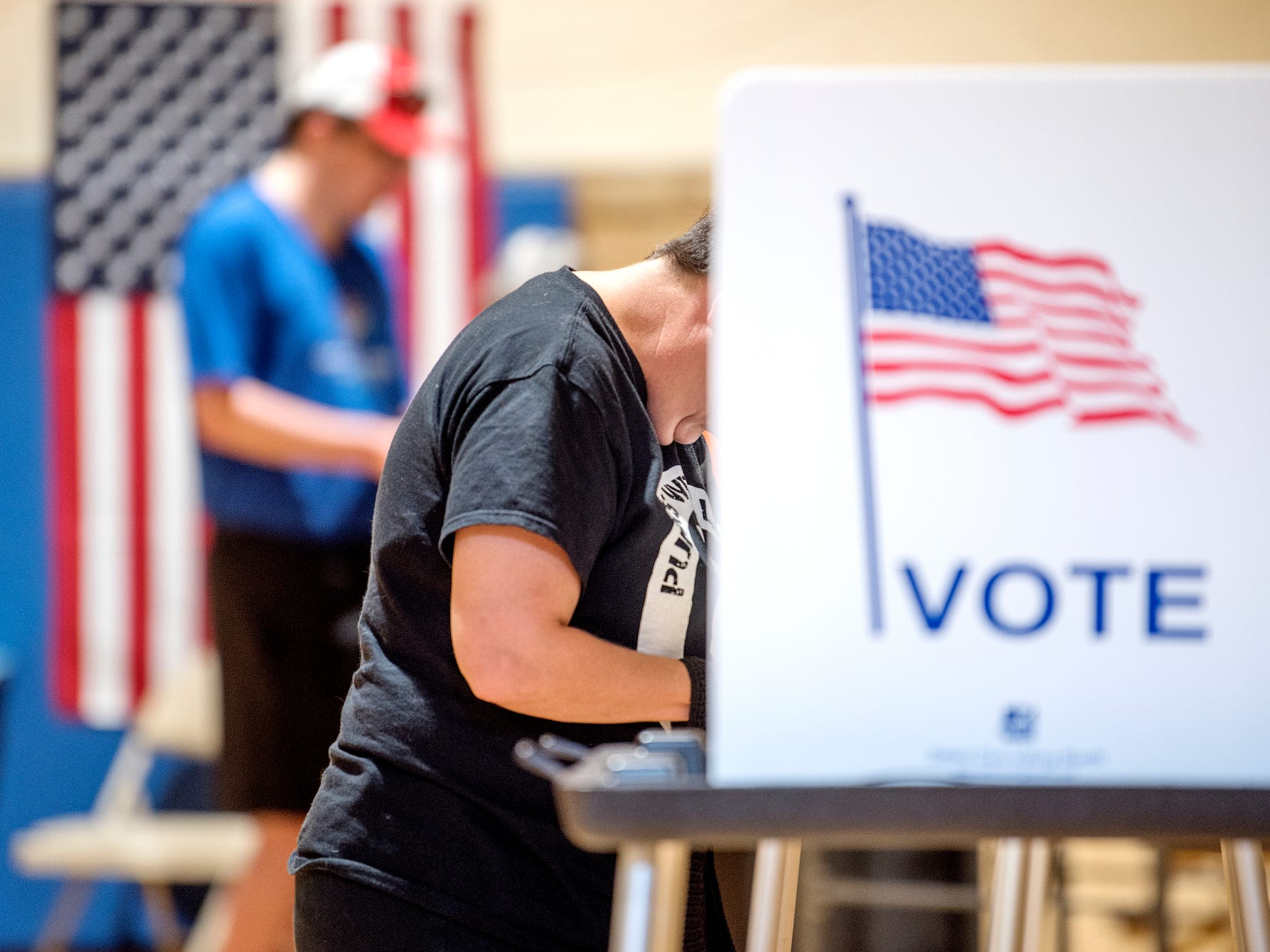 A voter fills out a ballot on Tuesday, Aug. 7, 2018, at the polling place inside the Foster Community Center in Lansing.
