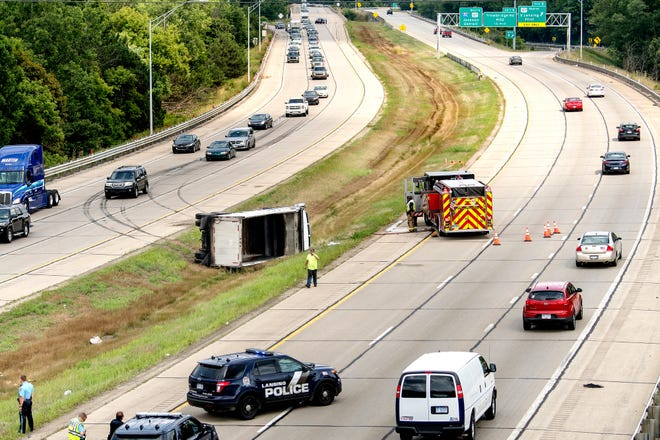 Police and fire personnel work the scene of a overturned dump truck in the median on I-496 looking west from the Aurelius Road bridge on Tuesday, Aug. 7, 2018, in Lansing.