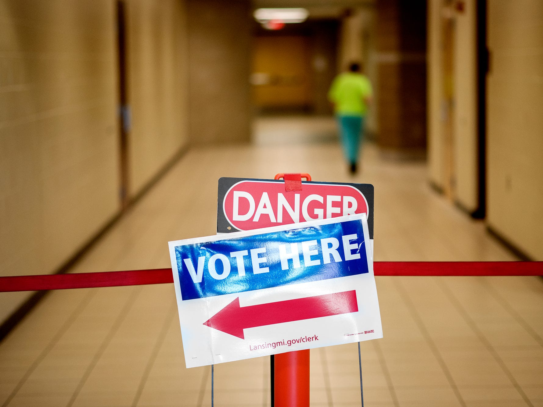 """A """"vote here"""" signs is placed in front of a """"danger"""" sign outside the polling place at Pattengill School on Tuesday, Aug. 7, 2018, in Lansing. Some areas in the building are blocked off due to construction on the school."""