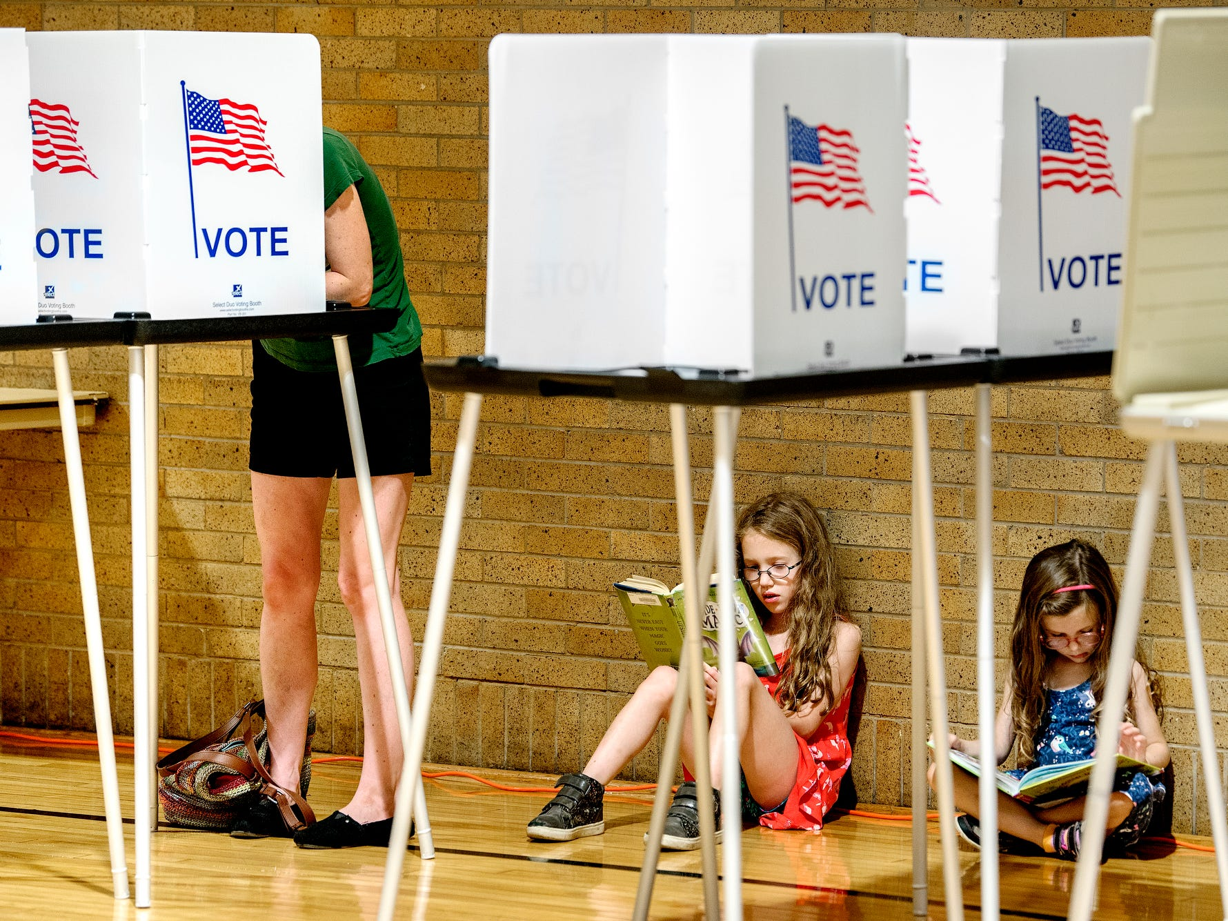 Seven-year-old November Moll, center, and her sister Selah, 4, right, read books as their mother Valerie votes on Tuesday, Aug. 7, 2018, at the Foster Community Center in Lansing.