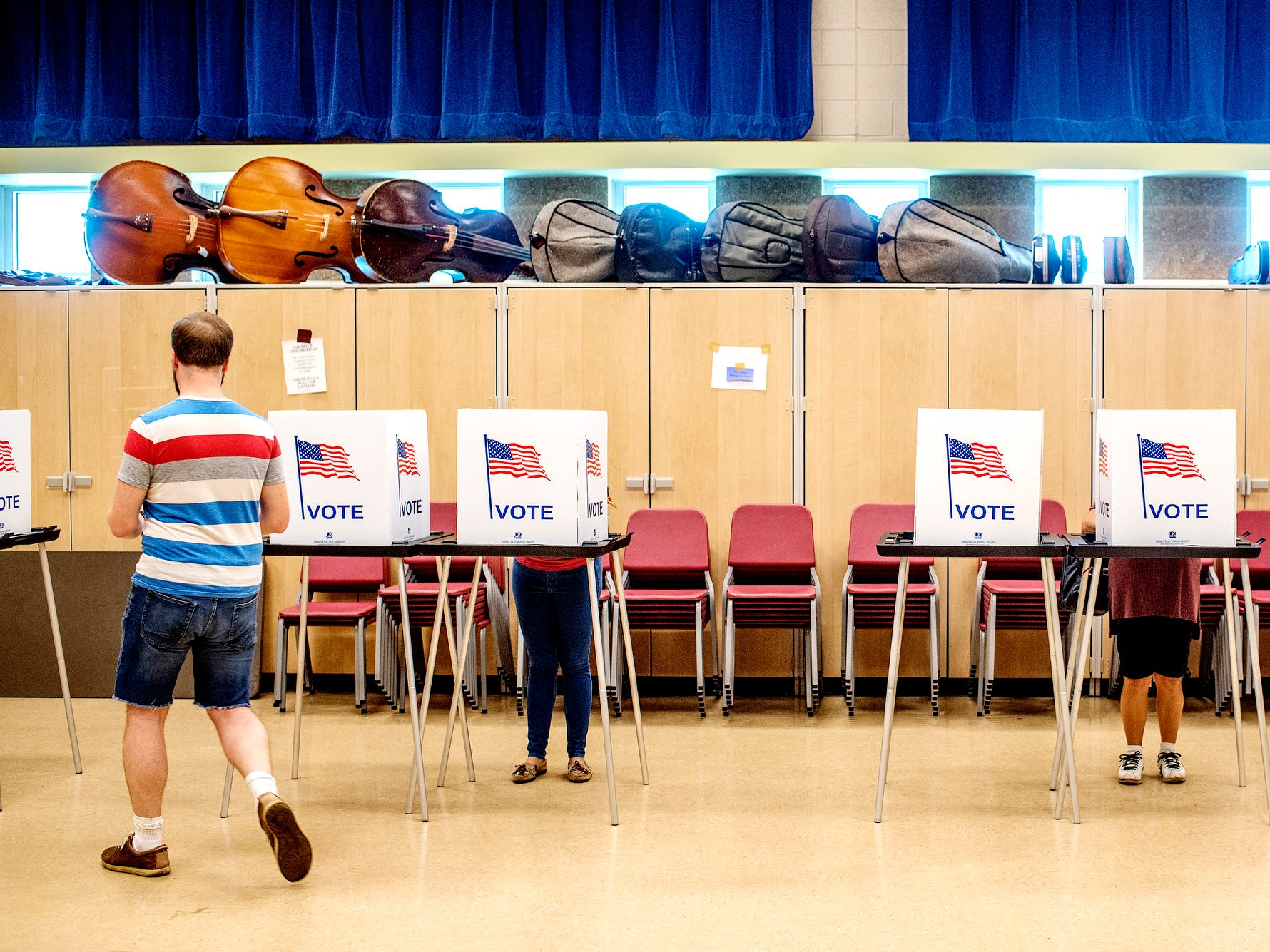 Voters fill out their ballots at a polling place in the band room at Pattengill School on Tuesday, Aug. 7, 2018, in Lansing.