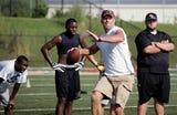 Former Green Bay Packers quarterback Brett Favre works with then Oak Grove High School football team.