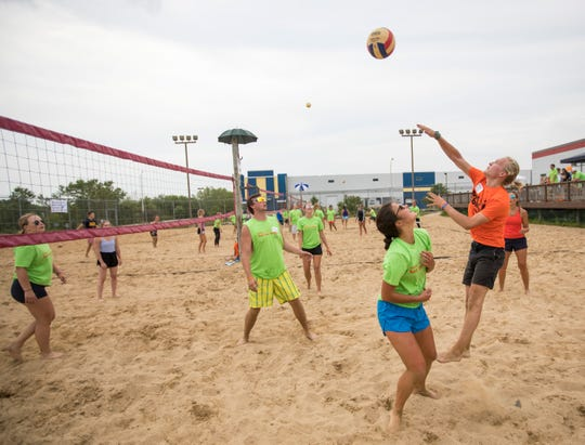 Charlie Sprinkman jumps and spikes the ball over to the opposing team during the first round of the volleyball tournament.