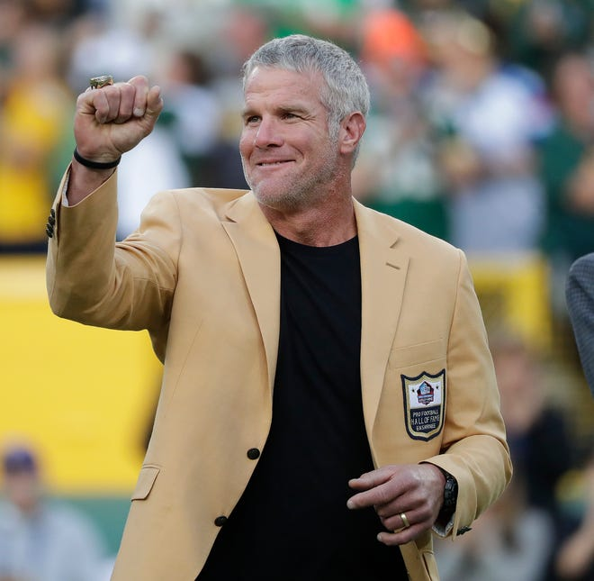 Brett Favre shows off his Pro Football Hall of Fame ring after receive it during halftime of the game against the Dallas Cowboys at Lambeau Field in 2016.