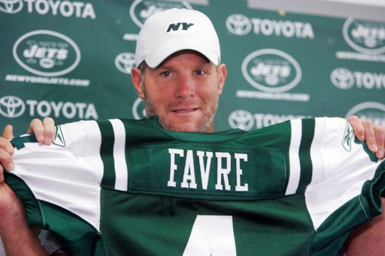 Brett Favre holds up his new New York Jets jersey at Cleveland Browns Stadium before an NFL exhibition football game between the New York Jets and Cleveland Browns Thursday, Aug. 7, 2008, in Cleveland. Favre was traded from the Green Bay Packers to the Jets earlier in the day. (AP Photo/Mark Duncan) ORG XMIT: OHMD101