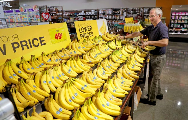 """Tom Haywood of Menomonee Falls selects some bananas at the Metro Market on County Line Road in Menomonee Falls on Tuesday. The Milwaukee-based Roundy's division of The Kroger Co. says it is cutting prices """"on thousands of items"""" at all of its Pick 'n Save, Metro Market and Copps stores in Wisconsin."""