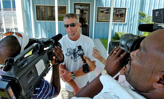 Brett Favre, center, talks to reporters after leaving left Green Bay, Wis., and arriving at Hattiesburg-Laurel Regional Airport near Hattiesburg, Miss., Wednesday, Aug. 6, 2008.