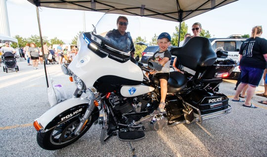 Three-year-old Matthew Owen of Muskego checks out the controls of a police motorcycle during National Night Out at the Franklin Public Library on Monday, August 6, 2018. The event featured law enforcement & fire emergency vehicles, safety Information, displays, demonstrations, face painting, refreshments and more.