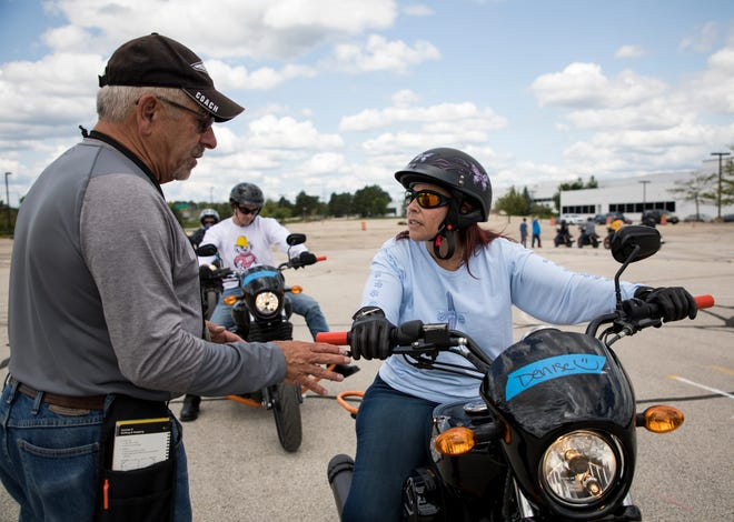 Jim Wiskerchen (left) talks to Denise Curran about the exercise the group is practicing during a class in a parking lot at the Harley-Davidson Powertrain Operations in Menomonee Falls.