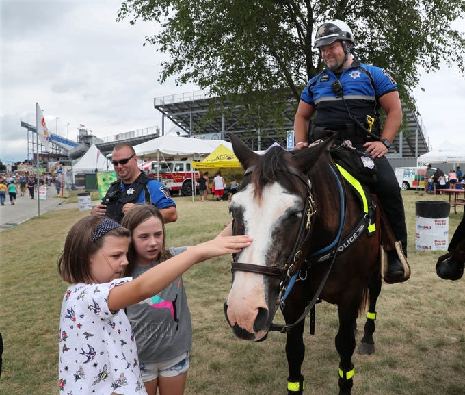 Jana Kotrly (left), 7, and her sister Audrey Kotrly, 9, of Brookfield, pet officer Nathan Anhalt's horse Lil Joe at the Wisconsin State Fair. The fair's mounted police patrol is celebrating  50 years of service.