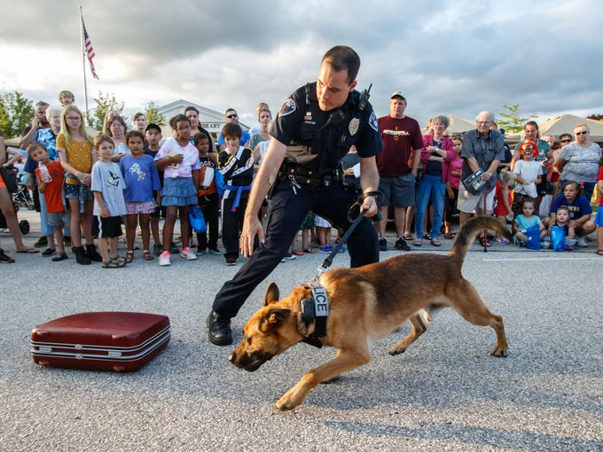 Franklin K-9 officer Mac Koster gives a drug search demonstration with his K-9 partner Vito during National Night Out at the Franklin Public Library on Monday, August 6, 2018. The event featured law enforcement & fire emergency vehicles, safety Information, displays, demonstrations, face painting, refreshments and more.