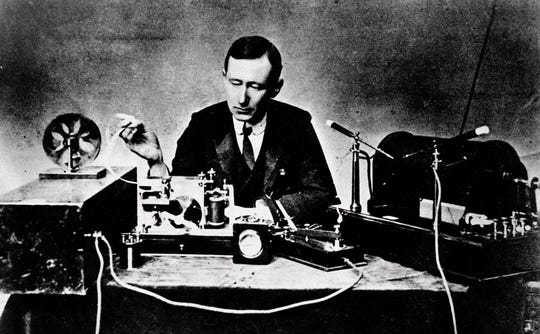 Italian physicist Guglielmo Marconi, who claimed he invented radio, reads signals on a tape recorder, left, with a 10-inch spark coil used for ship-to-shore radio tests in this 1901 file photo.
