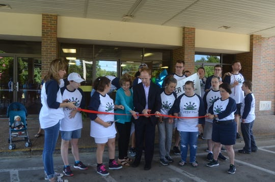 PEER Place students, staff, board members and Mayor Jamie Clary cut the ribbon for the new program for developmentally-delayed adults in Hendersonville.
