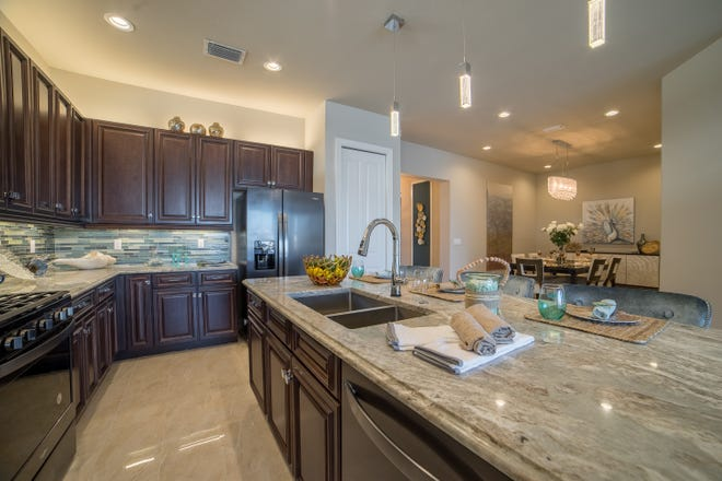 The chef-inspired kitchen in the Capri model includes an island counter, stainless steel appliances, granite countertops, pantry and natural gas.