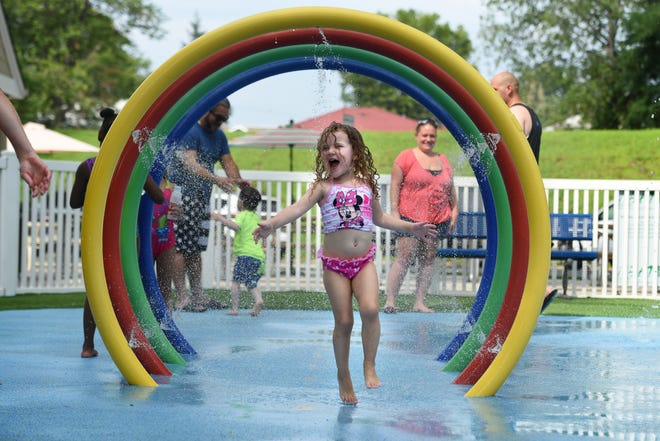 Aviana Corn 3, of Hawthorne, through beats the heat running through water rings at the Lyndhurst Spray Park located in Town Hall Park on Tuesday, August 7, 2018.