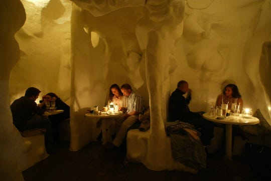 Couples have dinner in the cave area of the Archetypus Cafe.