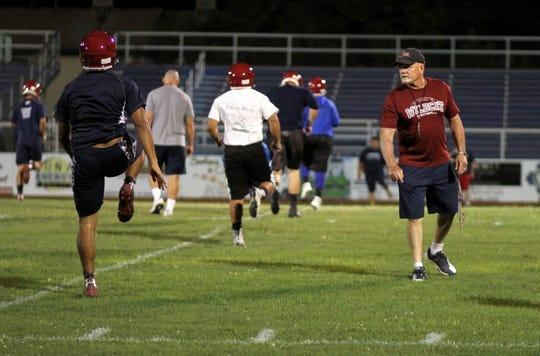 Coach Greg Simmons looks over the warm-ups during the first official day of Wildcat Football practice shortly after 12:01 a.m. on Monday, Aug. 6.