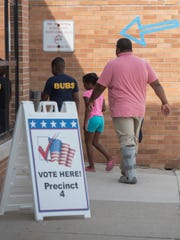 A voter and family enter Farmington High School to vote in the 4th precinct.