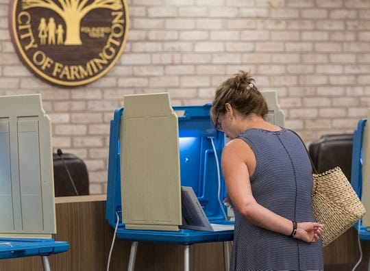 "Michelle Saxton, voting at precinct 1, Farmington City Hall, ponders her choices. She said, ""I couldn't decide. Too many good choices. It came down to today."""