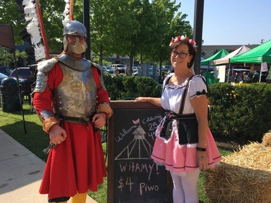 A 16th Century Polish Knight stands guard over the market while volunteer Mary Martin from the Greater Farmington Area Chamber of Commerce plays guest host to cultural fanfare.