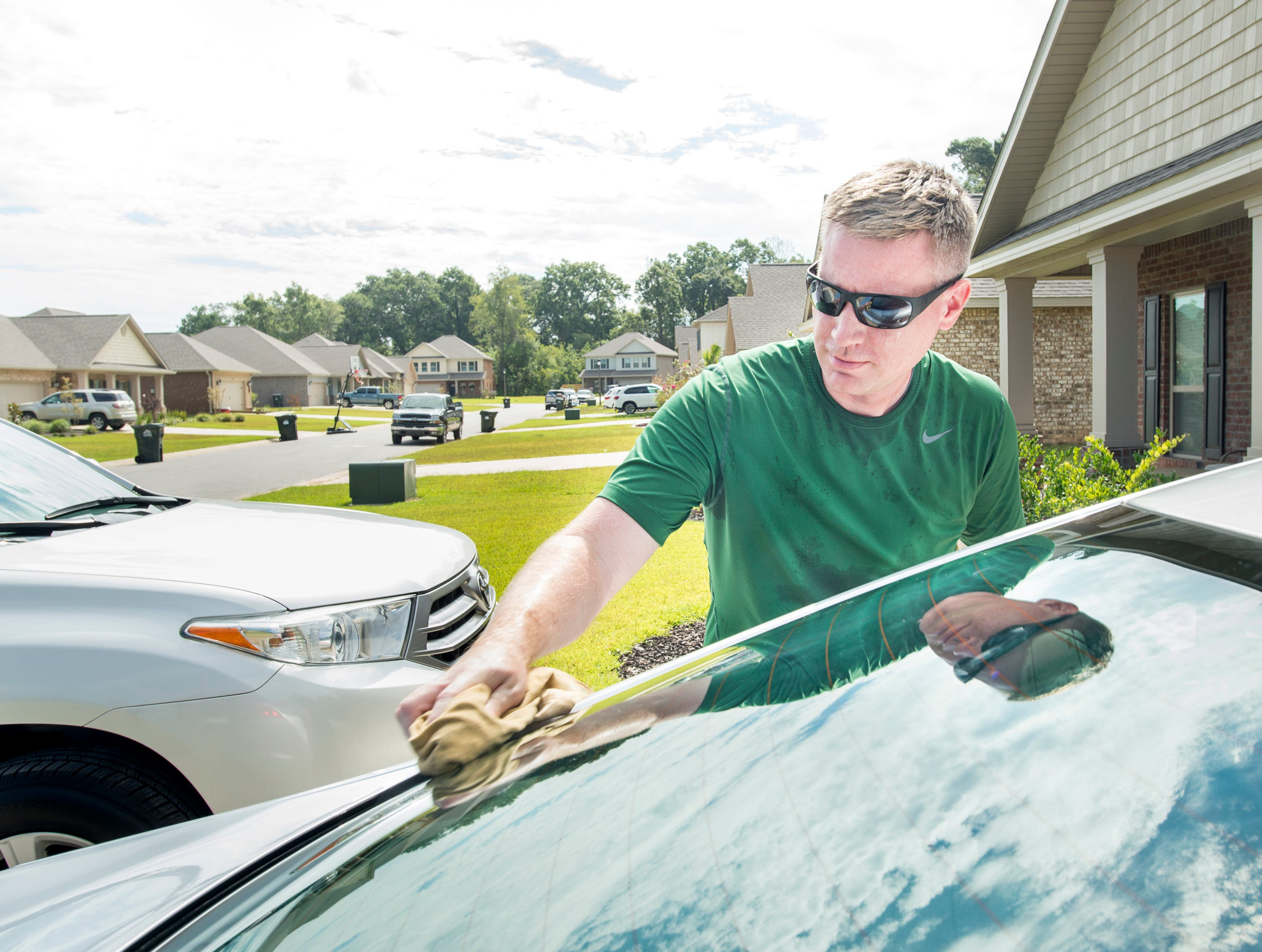 Jim Gormley cleans his car outside of his home in the new subdivision of Heritage Estates in Pace's District 1 on Tuesday, August 7, 2018.  Gormley was one of the first families to move into the neighborhood eight months ago.