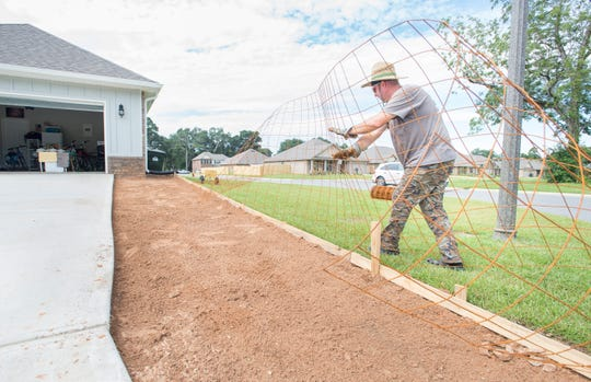 Paul Lassiter, of Paul's Hardcore Concrete, works on a driveway expansion at a home in the new subdivision of Heritage Estates in Pace's District 1 on Tuesday, August 7, 2018.