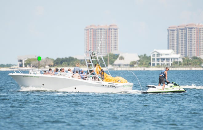 An outgoing parasail boat and an incoming waverunner pass off Pensacola Beach on Tuesday, August 7, 2018.