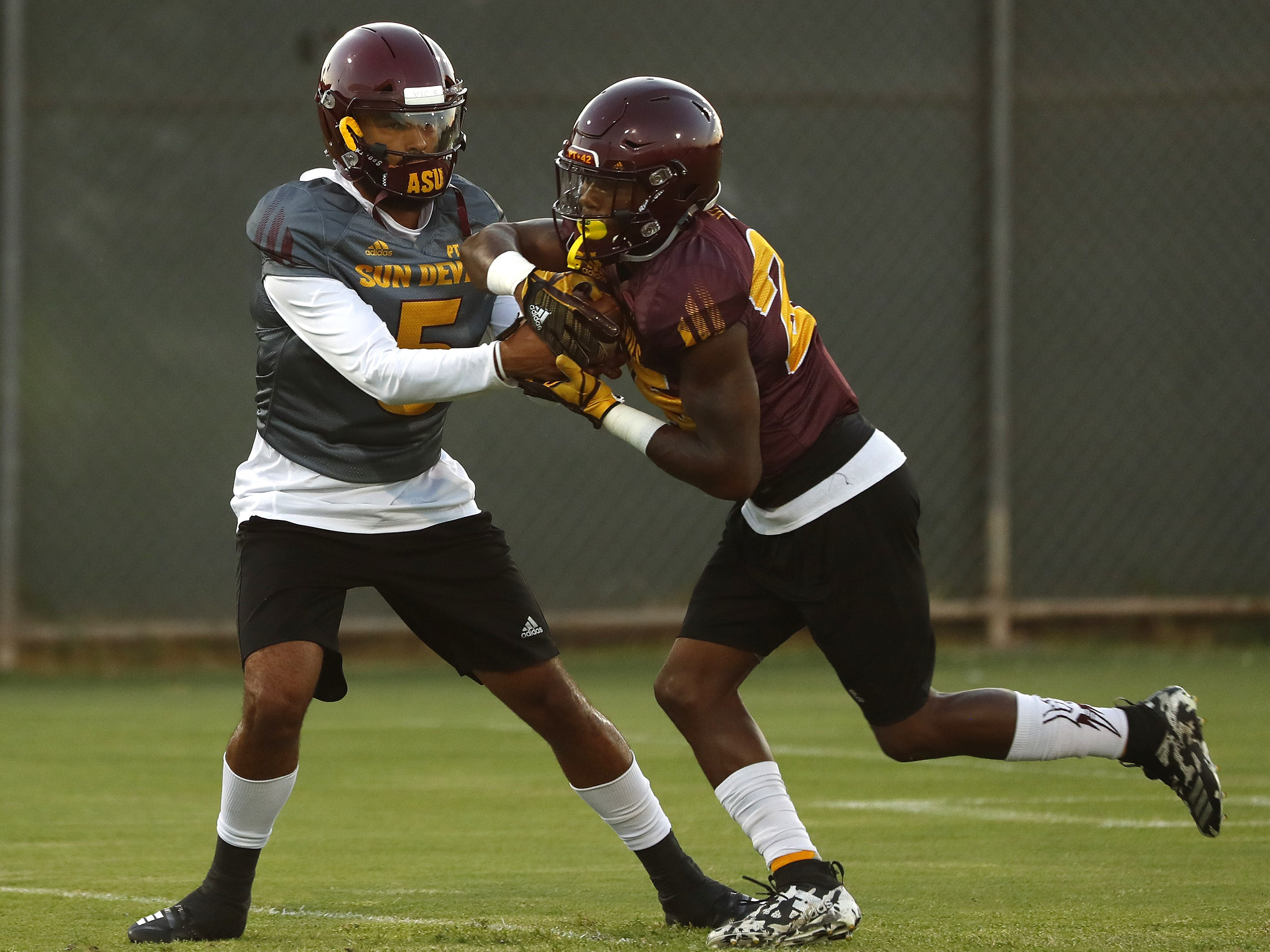 ASU's Manny Wilkins (5) fakes a hand-off to Trelon Smith (25) during a practice at Kajikawa Football Practice Fields in Tempe, Ariz. on Aug. 6, 2018.