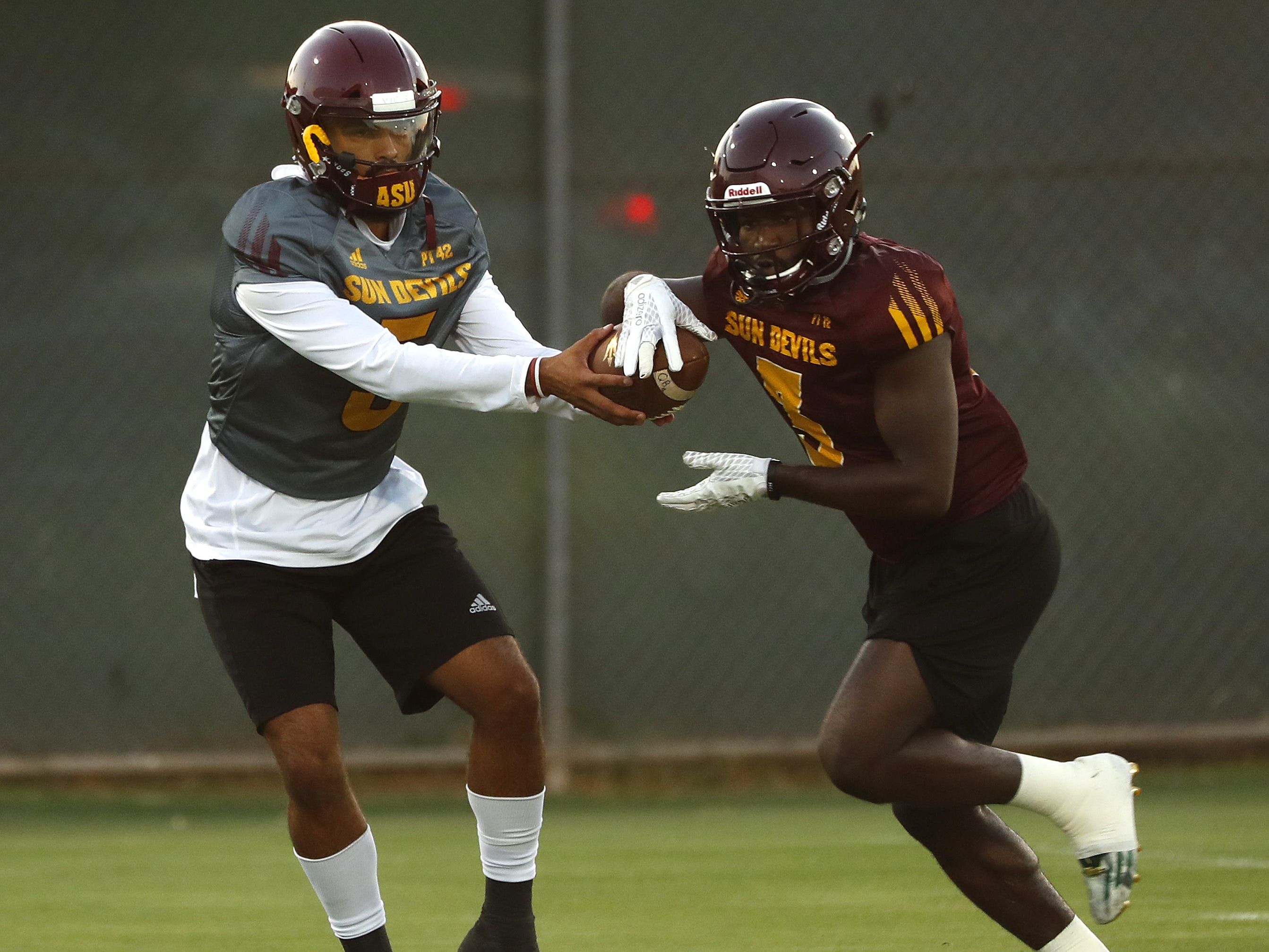 ASU's Manny Wilkins (5) fakes a hand-off to Eno Benjamin (3) during a practice at Kajikawa Football Practice Fields in Tempe, Ariz. on Aug. 6, 2018.