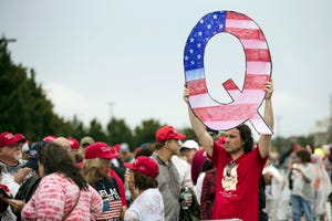 A member of a crowd waiting to enter a campaign rally for President Donald Trump in 2018 holds a Q sign to represent QAnon.