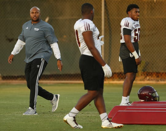 ASU's linebackers coach Antonio Pierce (L) instructs players during a practice at Kajikawa Football Practice Fields in Tempe, Ariz. on Aug. 6, 2018.